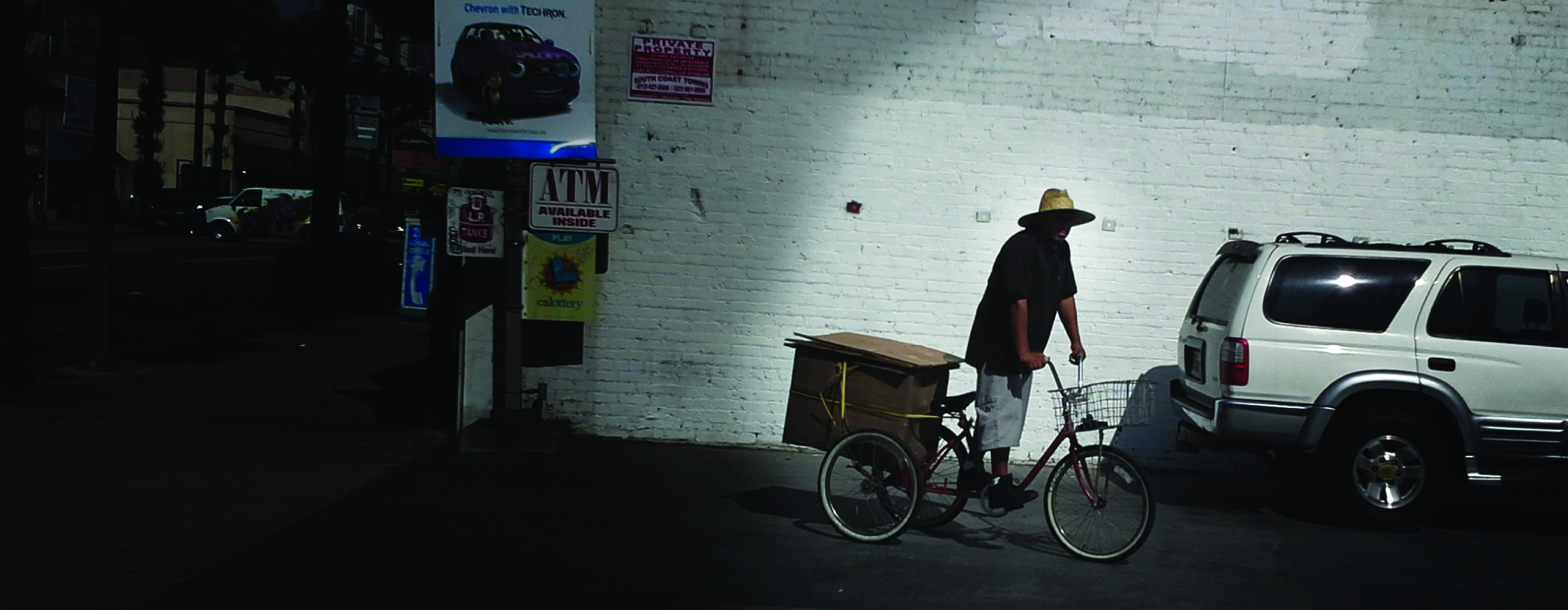 A man in a wide brim straw hat, his face in shadow, stands on top of a bicycle in a dark parking lot