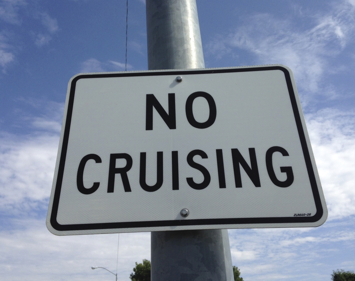 Street sign saying 'No Cruising' against blue sky background
