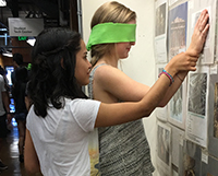One young woman guides another, who is wearing a blindfold, in feeling a wall